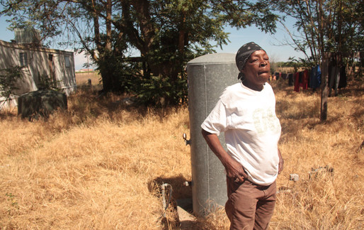 Flossie Ford-Hedrington stands beside her well, which stopped producing water last year (Sasha Abramsky). Image via thenation.com.