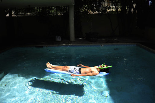 "Joseph Lee, 23, a UCLA graduate from Vallejo, teamed up with research partner Benedikt Gross to produce ""The Big Atlas of L.A. Pools."" Here he lounges in one of the blue oases. Susannah Kay / Los Angeles Times."