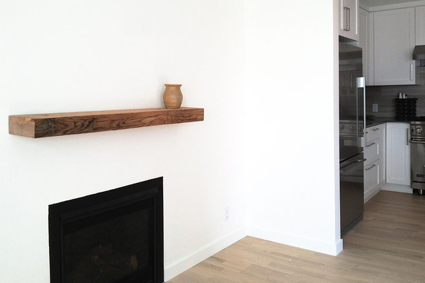 minimalist fireplace with reclaimed wood mantle at the main living space