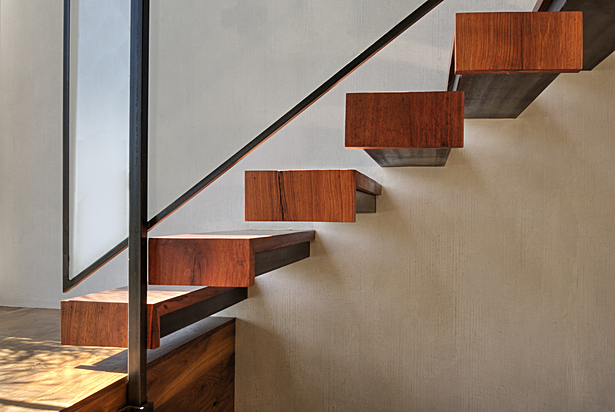 The floating staircase is made of 100-year-old teak, glass and blackened steel. The wood, from Berber World Imports in Culver City, was reclaimed and milled to fit the structural steel supports that are anchored in the wall.