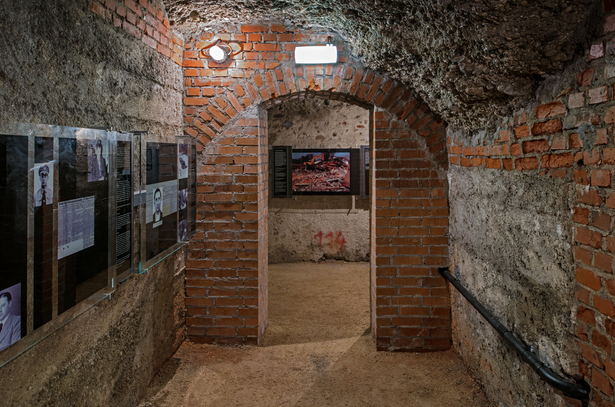 "Perpetrator Room: The exit from the room is narrowed by means of solid stone pillars under the load-bearing brick belt. These redundant ""supports"" built in place of the former 25 cm partition wall emphasise the impression of heaviness and oppression."