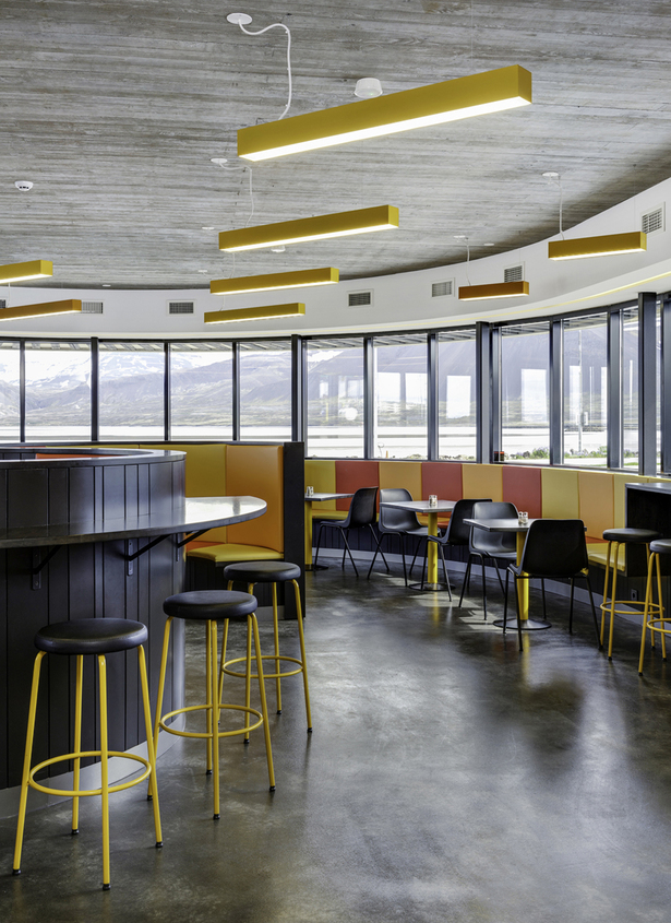 An elongated bar-desk transforms into seating arrangements and characterizes the semicircular restaurant