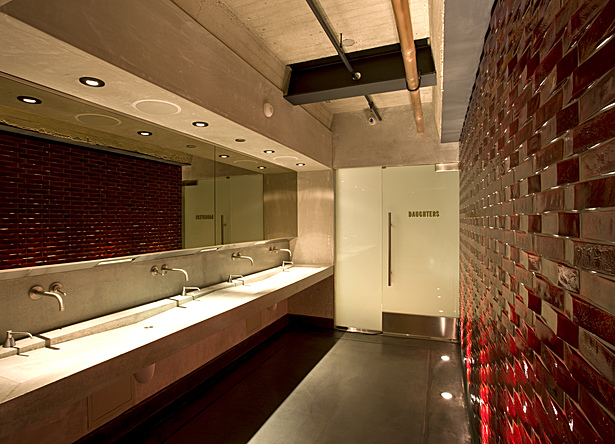 The architects at (fer) studio designed a community washroom which acts as a focal space for separate restrooms, with bock beer colored mosaic tiles, a bronze mirror and concrete sink.