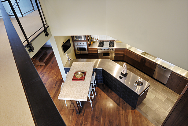 A double-height ceiling cutout and black walnut flooring connect the living area and the kitchen, which features a custom stainless-steel countertop and black slate floor. Cummins ordered the custom tabletop, which was made in China using smooth, cream-colored riverstones set in clear resin.