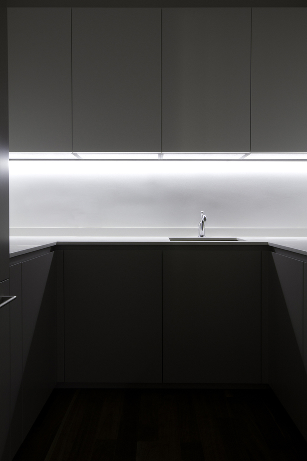 Hidden to the left is a small pantry of 6 square meters; despite its small dimension, the efficient design has made possible the inclusion of: refrigerator and freezer, microwave, oven, a secondary sink and more cabinets that enable the main kitchen to maintain its minimalist aesthetic and the clutter to be hidden away.