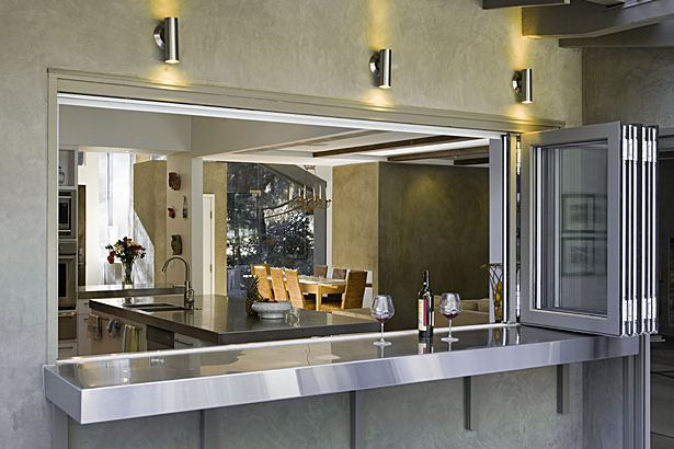 The kitchen was opened up to the rear garden through a stainless steel counter top that extends through the wall to an outside dining counter with a bifold window.