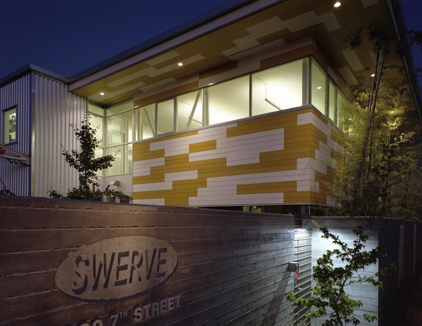Night view from 7th Street; recycled plastic siding on new addition in yellow and white.