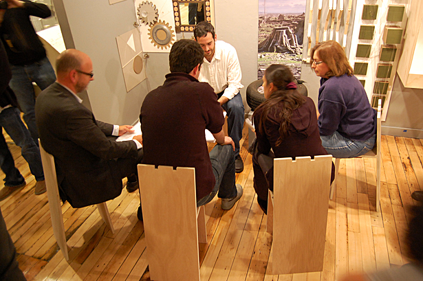 Chairs in use during critique allow for a conversation in the context of a crowded gallery.