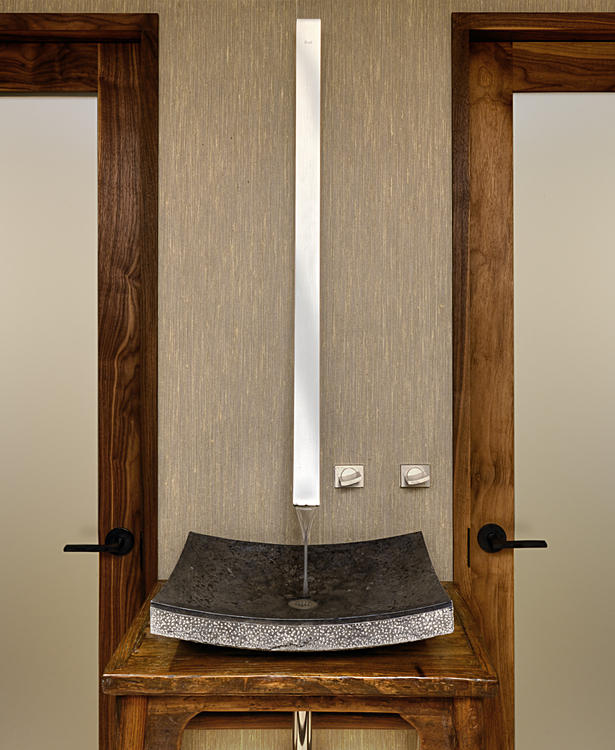 The powder room is defined by a long stainless steel wall-mounted fixture that emphasizes a single antique Asian table with a granite basin.