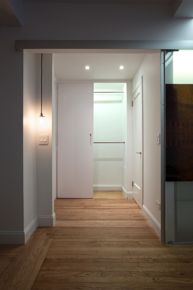 These doors in glossy white lacquer, not only are a sleek solution, but are also functional, since they can slide sideway, creating light plays that give depth to the small area that takes to the bathroom.