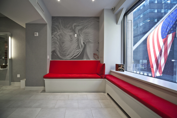 A bold red anchors the reception area against the chaos of the city street.