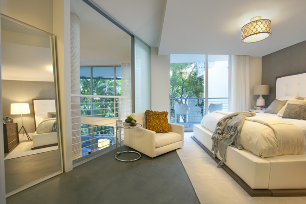 The master suite overlooks the twostory living space and is furnished simply. The king-sized bed has a tall headboard upholstered in tufted white leather and seems to float on a cream colored wool area rug.
