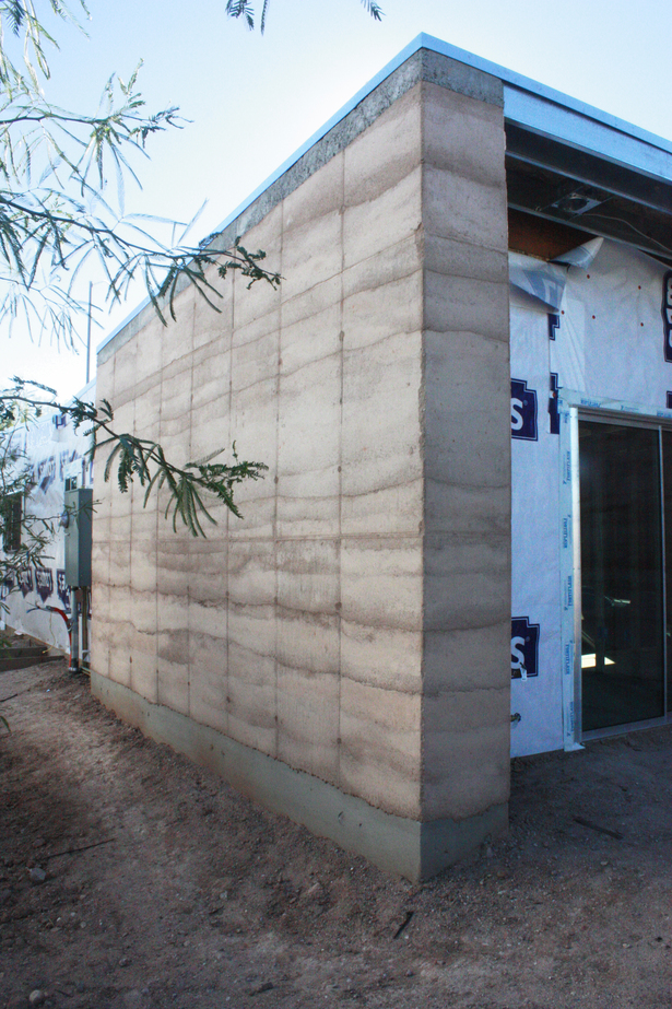 completed rammed earth wall + wood framed walls