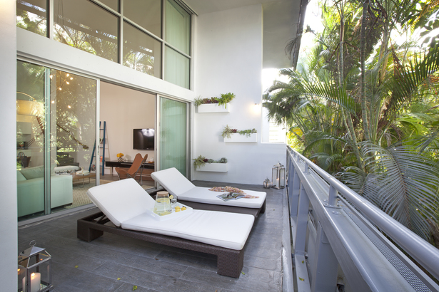 Looking out onto a side garden densely planted with tropical floiage, the wide deck has been finished with a porcelain tile with a wood-grain surface. the double sun chaise with built-in center table was sourced from Addison House.