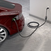 Plugged in: A Tesla Model S recharges at a standard outlet. (Image via technologyreview.com)