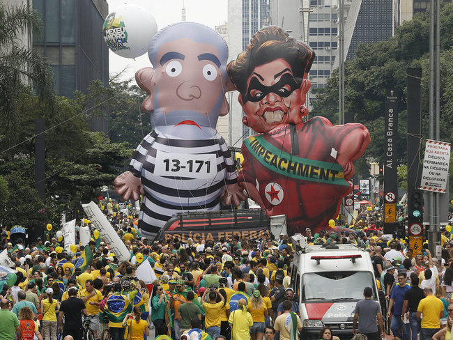 Demonstrators parade large inflatable dolls, depicting Brazil's former President Luiz Inacio Lula da Silva in prison garb and current President Dilma Rousseff dressed as a thief, in Sao Paulo on Sunday. Image by Andre Penner/AP via npr.org.