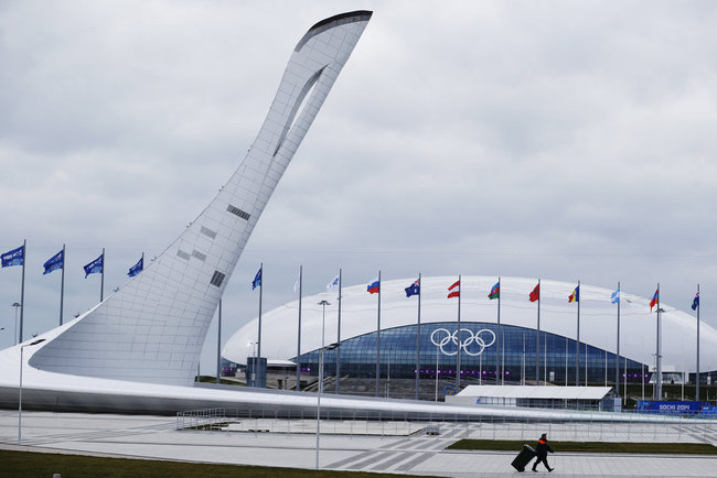 A worker walks past the Olympic torch and the Bolshoy Ice Dome in the Olympic Park as preparations continue Thursday ahead of the Sochi Winter Games. Russia has spent $50 billion on the 2014 games — the most expensive in history. (NPR/Pavel Golovkin/AP)