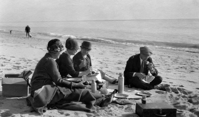 A 1925 photo of picnickers sitting on the Santa Monica shoreline. Image via Homestead Museum.