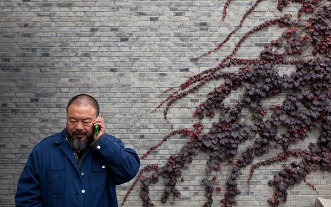 Ai Weiwei talks on his mobile phone at his studio in Beijing. (Aeon; Photo by Adam Dean/Panos)