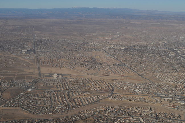 "Antonia Malchik argues in her aeon essay, The end of walking, that ""Americans have been stripped of the right to walk, challenging their humanity, freedom and health."" (Aerial photo of Albuquerque, New Mexico by Joe Mabel/Wikimedia Commons.)"
