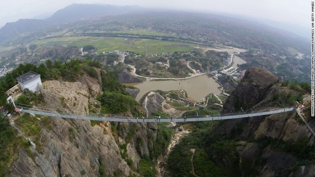 Originally made of wood, the bridge in China's Shiniuzhai National Geological Park has been converted to a glass walkway to attract a growing crowd of thrill seekers. (Image via cnn.com)