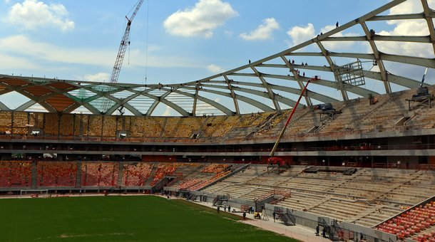Workers are seen in the roof as construction continues at the Arena Amazonia on December 10, 2013 in Manaus, Brazil. The stadium will host matches during the 2014 FIFA World Cup Brazil. (Michael Heiman/Getty Images via Marketplace)