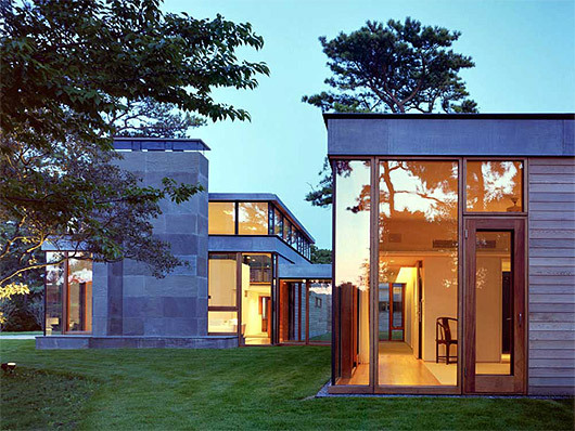 The Rifkind House in Wainscott, NY, a Long Island Modernist triptych pavilion clad in warm cedar siding, balanced with cool New York bluestone. Mahogany floor-to-ceiling window frames and custom-designed cherrywood furniture make the house an inviting and convivial entry into the pantheon of Modernist glass-walled houses. (Image via twbta.com)