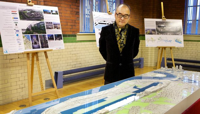 Xu Weiping, with a model of the Royal Albert Dock plans. Hazel Thompson for The New York Times