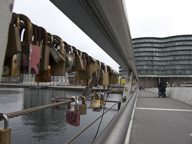 Padlocks, keylocks and combination locks string a bridge in Copenhagen
