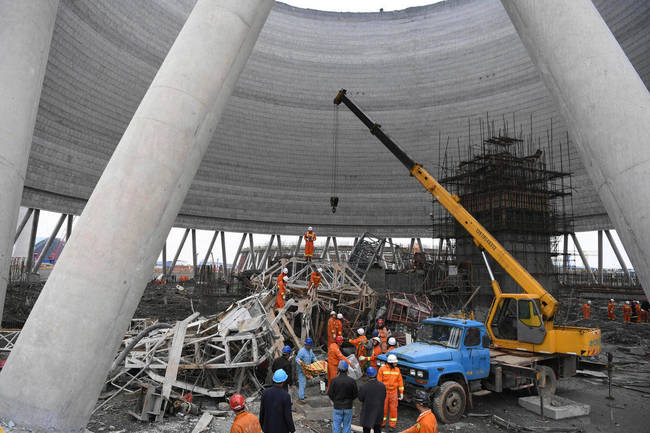 In this photo released by Xinhua News Agency, rescue workers look for survivors after a work platform collapsed at the Fengcheng power plant in eastern China's Jiangxi Province, Thursday, Nov. 24, 2016. State media reported dozens were killed after the scaffolding tumbled down. (Wan Xiang/Xinhua via AP)