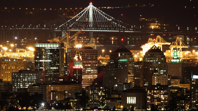 OAKLAND, CA, USA - Night Skyline with Bay Bridge. Image via Wikipedia.