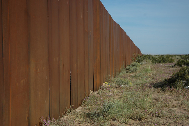 An existing segment of the US/Mexico border. Image via flickr.