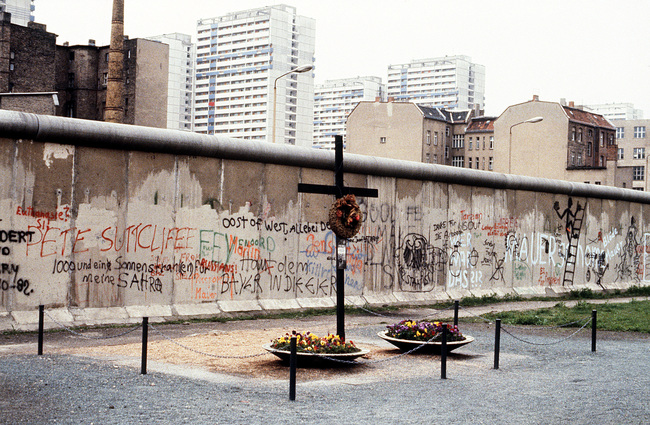 A memorial on the western side of the Berlin Wall dedicated to Peter Fecter, a young man who died while attempting to flee East Berlin (1984). Image via Wikipedia.
