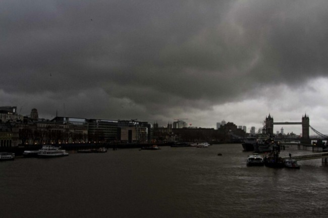 Dark clouds gather over Canary Wharf and Tower Bridge. Image for Rex Features via independent.co.uk