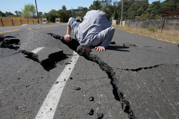 A man sticks his head in a rift opened up in the street by the Napa earthquake. Credit: Lisa James / Register