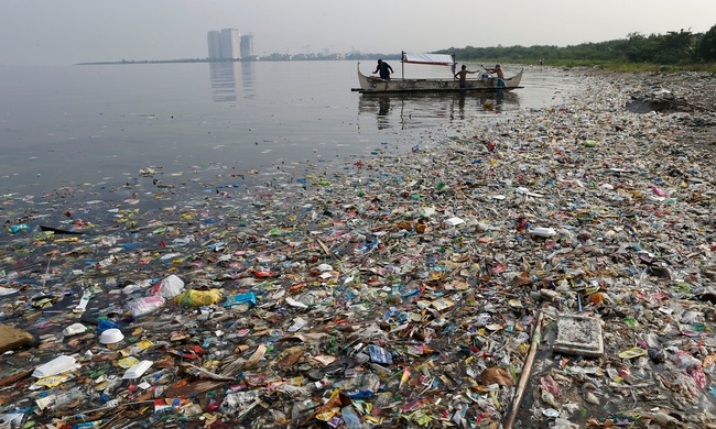 Fishermen float onboard a boat amid mostly plastic rubbish in Manila Bay, the Philippines. Humans have introduced 300m metric tonnes of plastic to the environment every year. Photograph: Erik de Castro/Reuters, via theguardian.com