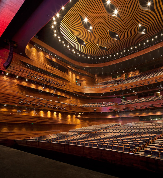 The main auditorium holds 1680 seats. The curved walls are made of 16.000 CNC cut solid bamboo blocks. The golden ceiling reflector design is inspired by the tradition Chinese opera mask. (Photo: Kari Palsila)