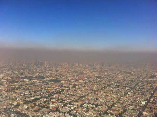 A layer of photochemical smog blankets Mexico City. Image via wikimedia.org