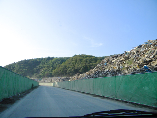 Piles of Debris on our way to Onagawa Temporary Housing about atleast 2 kilometers at an average of 25' high.... Literally a sh*t ton of trash with nowhere to go..for now I hope. via John Tubles
